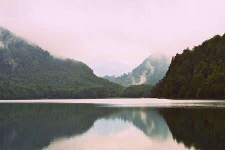 Beautiful mountain lake Alpsee - Hohenschwangau on an early foggy morning. Bavaria, Germany