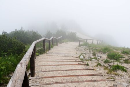 Stairway high in alpine mountains on a foggy morning. Stockfoto - 137677760