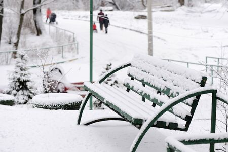 Green wooden bench covered with snow on a city street on a winter day