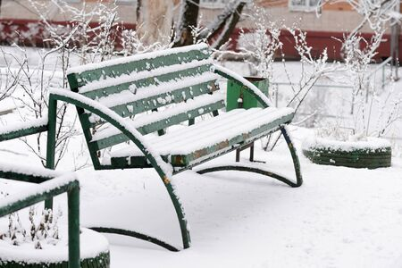 Green wooden bench covered with snow on a city street on a winter day Stockfoto - 137852356