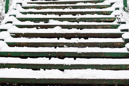 Green stairs covered with snow after a snowfall on a city street on a winter day Stockfoto