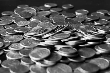 American cents on an old black wooden surface close-up. Monochrome money background