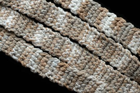 Melange yarn crocheted tape on a black background close up. Handmade concept. Top view