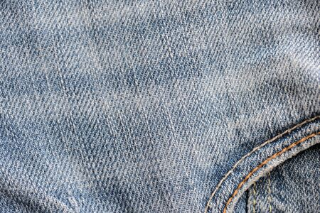 Old torn blue jeans texture close up, top view. Denim background