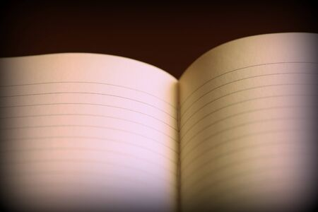 Open notebook with lined pages on a dark background. Retro style toned, vignetting