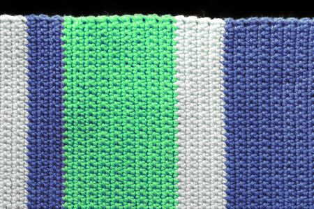 Fragment of a crocheted fabric close-up. Top view, copy space. Handmade background