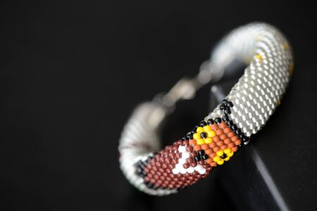 Beaded crochet gray bracelet with an image of an owl on a dark background close up. Hobby and leisure concept Stockfoto