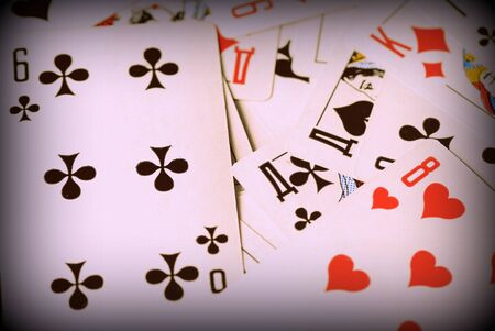 Playing cards scattered on the table close-up. Retro style toned, vignetting