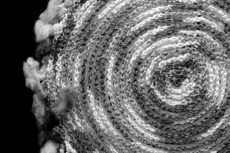 Fragment of a crocheted circle from melange threads based on a plastic canvas from the wrong side close-up. Black and white Stockfoto