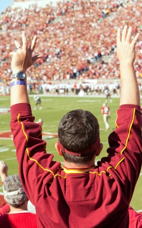 tallahassee: Tallahassee, Florida, USA - October 22, 2011:  Florida State football fan stands up and cheers at a home game as the FSU Seminoles play the Maryland Terps at Doak Campbell Stadium. Editorial