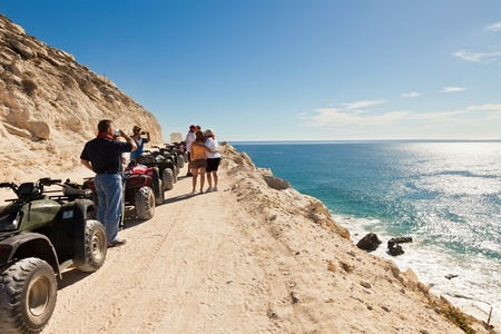 Cabo San Lucas, Mexico - February 12, 2011:  Guests of an ATV tour enjoy a rest and the coastline of the Sea of Cortez.  These ATV tours take riders from the desert terrain to the sea.