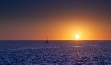 Sunset on the Sea of Cortez with sailboat on the horizon photo