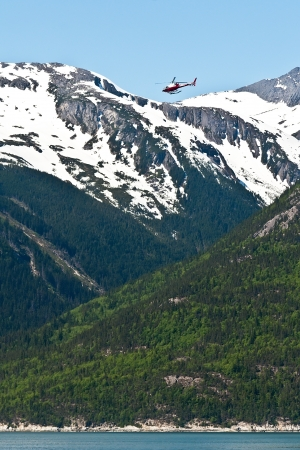 overs: Helicopter fly overs are common when visiting Skagway, Alaska Stock Photo