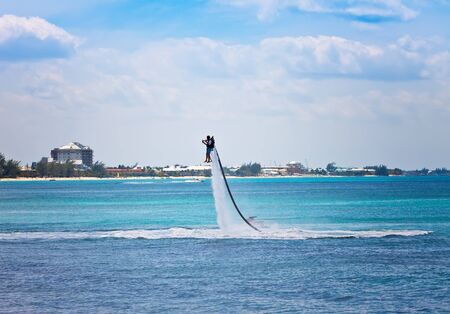 cayman islands: Man uses water jet pack on the Caribbean in the Cayman Islands