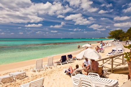 excursions: Grand Cayman, Cayman Islands - Mar. 8, 2013:  Tourists enjoy the popular Seven Mile Beach in Grand Cayman.  The beach is a local tourist attraction, offering many luxury resorts, restaurants and water sport excursions. Editorial