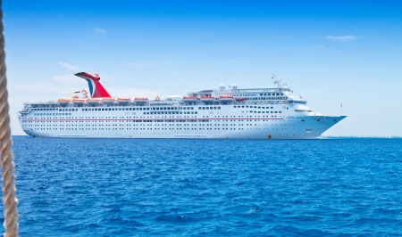 luxuries: Grand Cayman, Cayman Islands - July 13, 2011:  Carnival Cruise Lines ship, the Inspiration, anchored off shore on Grand Cayman. The ship is of the oldest Fantasy-class Carnival ships, and has been considered fine for short inexpensive getaways. Editorial