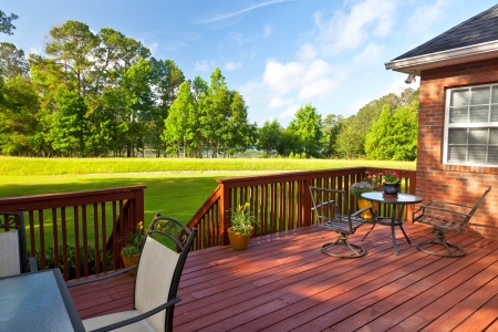 Residential backyard deck overlooking lawn and lake Stok Fotoğraf