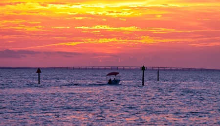 destin: Small fishing boat on the Gulf of Mexico at sunset in Destin, Florida Stock Photo