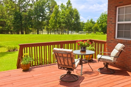 Residential backyard deck overlooking lawn and lake photo