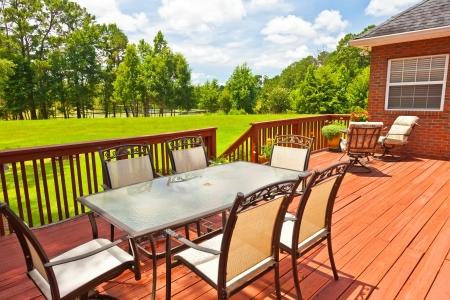 Grote residentiële houten achtertuin terras met meubilair Stockfoto