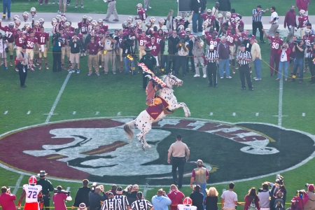 Tallahassee, FL - Nov. 24, 2012:  Florida State football mascot, Chief Osceola on his horse Renegade, mark the beginning of the football game by throwing the flaming spear at midfield.