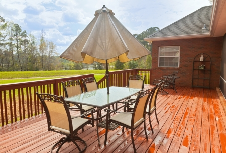 stained: Large wooden backyard deck with patio furniture and a view of lake