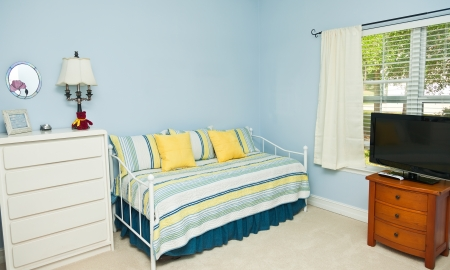 Blue colored walls in a bedroom with a daybed, TV, and dresser
