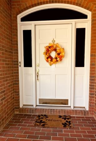 Decorative autumn wreath on a white front door Stock Photo