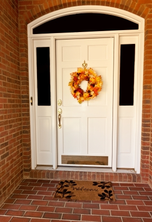 Decorative autumn wreath on a white front door Standard-Bild