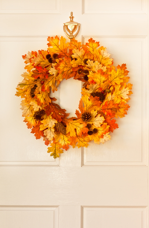 Decorative autumn wreath hanging on front door photo