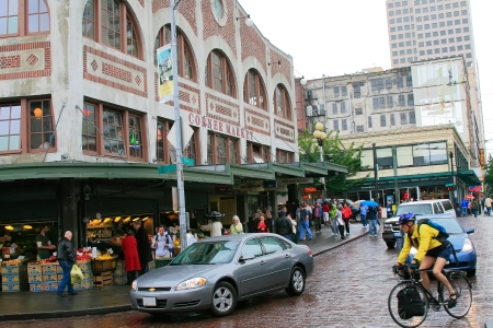market place: Seattle, WA - June 9, 2007: Merchants and tourists at the famous Pike Place Market in Seattle.  This public market opened in 1907 and continues to be one of the oldest public farmers market in the USA.
