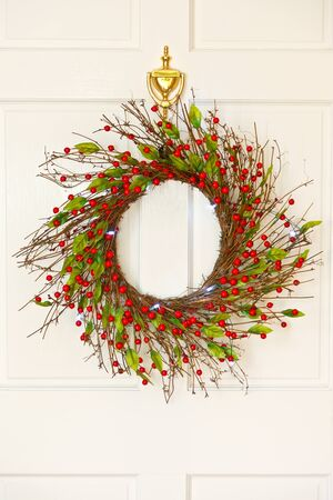 door leaf: Decorative Christmas wreath on a white front door