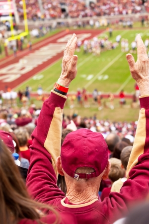 Tallahassee, FL - Nov. 16, 2013:  Elderly Florida State fans raises his hands for touchdown at FSU vs Syracuse University football game at Doak Campbell Stadium.