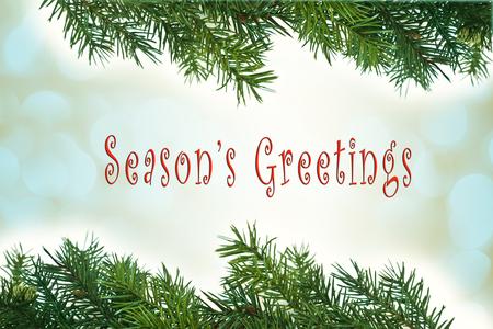 Kerstkaart met groene pijnboomtakken en de tekst van de Groeten van het seizoen