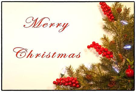 merry christmas text: Tarjeta de Navidad con bayas rojas, ramas de pino, las luces y el texto Feliz Navidad Foto de archivo