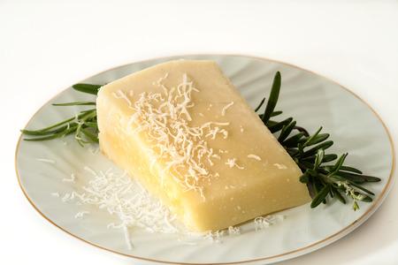 queso rallado: Una cuña de queso Pecorino Romano, simplemente rallado, con una ramita de tomillo en un plato