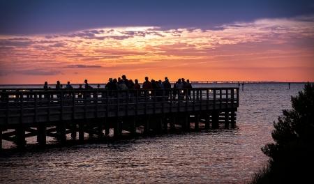 destin: Pier overlooking sunset over the horizon in Destin, Florida Stock Photo