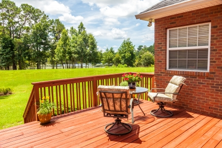 Backyard deck overlooking lake outside residential structure Stock Photo