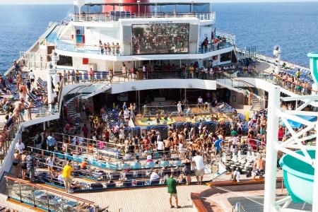 schepen: Caribische Zee, 10 juli 2011: Passagiers aan boord van de Carnival Freedom te verzamelen op het Lido Deck bij de start van een Caribische cruise. De Freedom is de vijfde 110.000-ton zware schip, eigendom van Carnival. Redactioneel