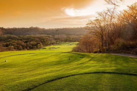 日没で美しい熱帯ゴルフコースの風景 写真素材