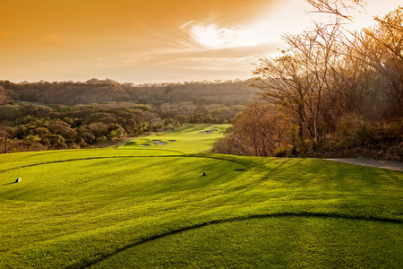 Paysage d'un beau terrain de golf tropicale au coucher du soleil