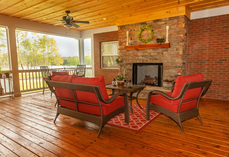 Screened backyard deck with fireplace overlooking lake