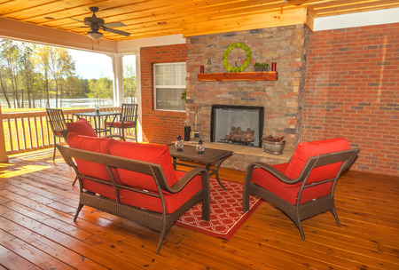 Screened in backyard deck with furniture overlooking lake