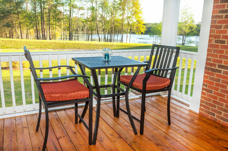 Screened in backyard deck with furniture overlooking lake photo