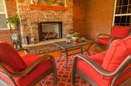 Seating area around gas stone fireplace on a covered backyard deck