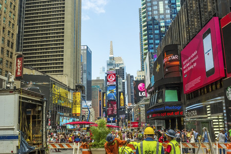 times square: New York, NY - June 24, 2014:  Pedestrians and constructions workers fill NYCs Times Square, the junction of Broadway and 7th Avenue, and the center for worldwide entertainment.