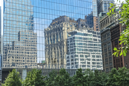 manhattan mirror new york: Reflection of New York City architecture from the side of a glass building in lower manhattan.