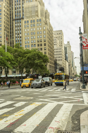 New York, NY - June 23, 2014:  Midtown city street, near Fifth Avenue, in New York City.  Filled with pedestrians and traffic on a daily basis. Редакционное