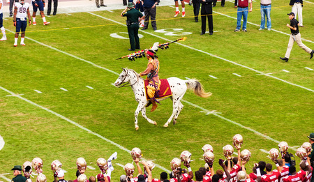 college football: Tallahassee, FL - Nov. 16, 2013:  FSU mascot, Chief Osceola, riding his horse Renegade, takes the field to official start the football game, a long time tradition in the Seminole nation.  The Florida State Seminoles completed the season by winning the 201