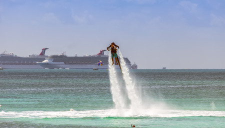 Grand Cayman, Cayman Islands - Mar. 8, 2013:  An unidentified man demonstrates the water jet pack in the Caribbean near Seven Mile Beach.  Seven Mile Beach is the main tourist attraction on the island, bringing in numerous water sport activities.